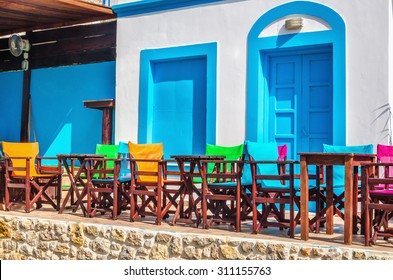 View on typical Greek modern blue and white restaurant with colorful chairs and tables, Greece