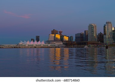 A view on Vancouver city skyline from Stanley Park at sunset, Canada. Urban downtown panorama along the coastal harbor line.