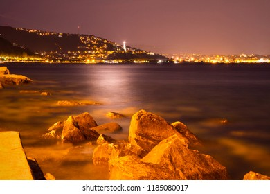 View on Vittoria Light and Trieste by nigt. Night photo, panorama of the city, city lights, Adriatic Sea landscape by night and coastline with rocks and night lights. Italy coast.