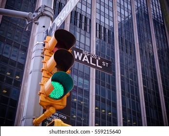 View on wall street yellow traffic light with black and white pointer guide. Green traffic light to Wall street banks money dollars finance offices. New York traffic light on Wall street money