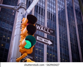 View on Wall street yellow traffic light with black and white Wall street, One way pointer guides. Green traffic light one way to Wall street banks money dollars finance New York Stock Exchange NYSE