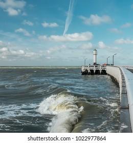 View on waves and old wooden pier of Nieuwpoort, Belgium.