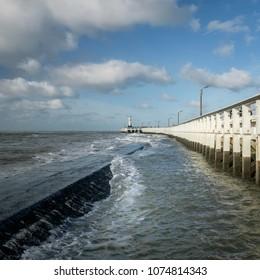 View on waves and old wooden pier in Nieuwpoort, Belgium.