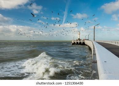 View on waves and old wooden pier of Nieuwpoort in Belgium.