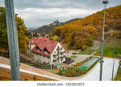 View on Wernigerode castle over fall jump with foliage coloring in dark sky, Harz National Park, Germany
