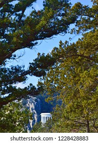 View on white colonnade on rocks trough trees branches, green branches of pine, blue sky