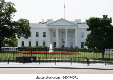View on the white house during the summer day. Residentce of the president of United States of America. The architecture of the modern city. White building with columns and green lane with a fontaine