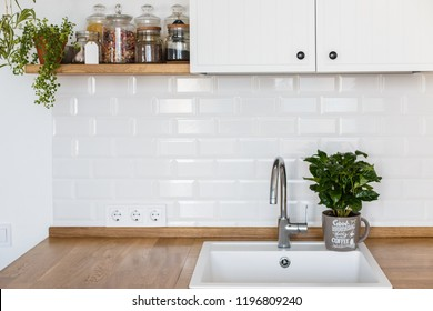 View on white kitchen in scandinavian style, kitchen details, coffee tree plant on wooden table, white ceramic brick wall background