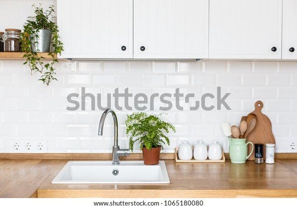 View on white kitchen in scandinavian style, kitchen details, plants on wooden table, white ceramic brick wall background