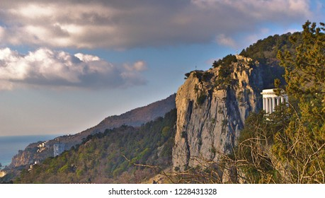 View on white seaside colonnade on rocks  trough trees branches, green branches of pine, blue sky