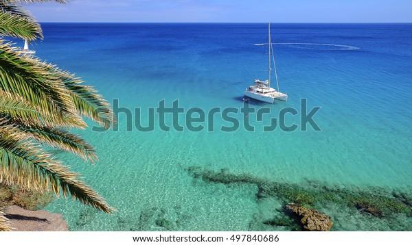 Blick auf ein weißes touristisches Schiff in blauer Lagune des Atlantischen Ozeans, geschlossen am Strand Playa de Morro Jable in Fürteventura, Spanien.