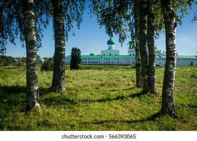 View on the white walls of an old orthodox monastery through a birch grove