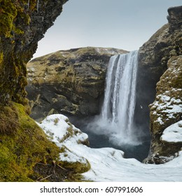 View on winter Skógafoss waterfall in Iceland - green and grey mosse in foregrund