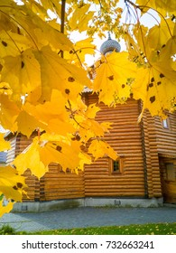 View on wooden church through maple tree foliage in Indian summer