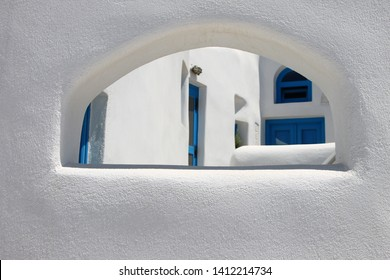 View on the yard through an arch window. Mediterranean village with stone houses and small wooden wickets.  Traditional greek architecture.
