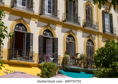 View on the yellow building facade decorated with windows small balconies during sunny day. The architecture of Spanish City, Malaga, Spain