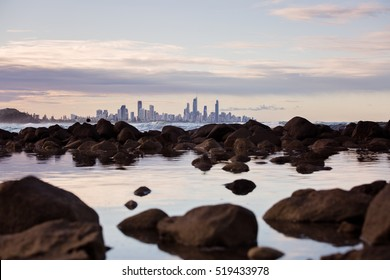View from one of Australia's famous Gold Coast beaches, Burleigh Heads looking up over rocks with Surfer's Paradise on the skyline. Very calm and tranquil with adjusted exposure for copy space.