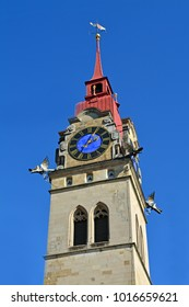 View of one the colourful 18th century twin towers of Winterthur's town church in Switzerland with a red spire and blue clock disc.