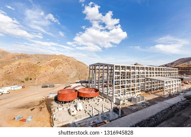 View of the ongoing industrial copper processing plant. Brown thickener tanks and concrete columns and beams that appear in the section, flotation building.