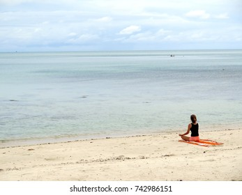 View of only one Female doing meditation on serene Beach, Holiday Concept