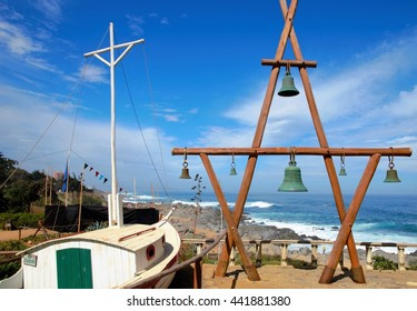View onto the ocean outside of Pablo Nerudas house with a wooden construction with green bells and a white boat in the foreground