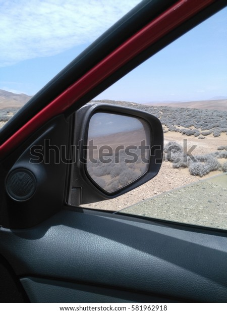 View from open car window to desert
