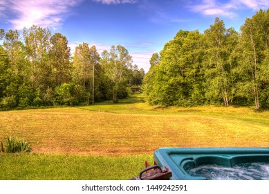 A view of an open field surrounded by trees, from the hot tub.