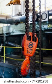A view of an orange 8 ton maximum weight crane hook at an abandoned paper mill in Hamilton, Ohio.