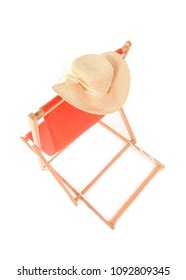 View of Orange Deckchair from above with cream straw hat hanging from it. Space for text.