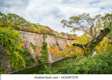 View of Osaka Castle tower roof from Osaka Castle Park, fortifications and Outer Moat in autumn in Kansai region, Japan.