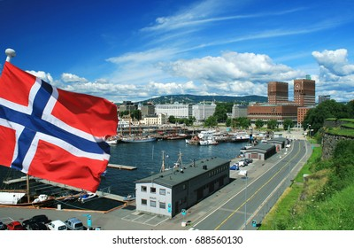 View of Oslo city harbor with flag of Norway in front
