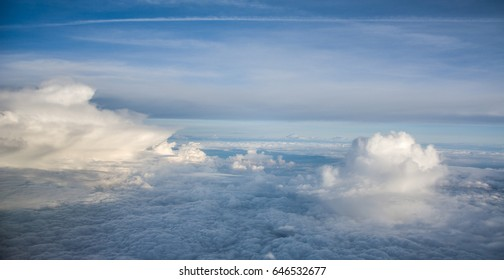 View out of airplane on white clouds and blue sky