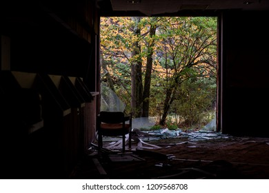 A view out of a broken window towards Autumn colored foliage at a derelict and abandoned Poconos Mountain resort in Pennsylvania.