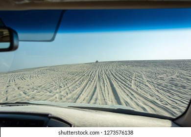 View out of a car windshield on a dune driving tour in Khor Al Adaid desert in Qatar.