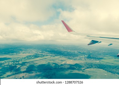View out of plane's window, with a plane wing and landscape view underneath