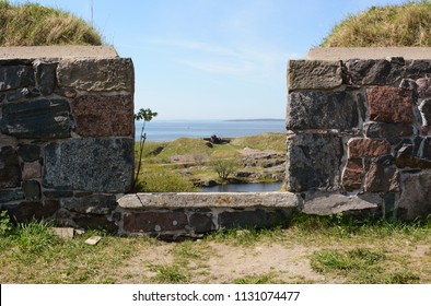 View out to sea through thick castellations in a defensive stone wall on Suomenlinna sea fortress