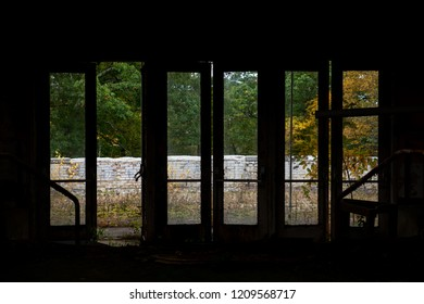 A view out of several doors towards colorful Autumn blessed trees at a derelict and abandoned Poconos Mountain resort in Pennsylvania.