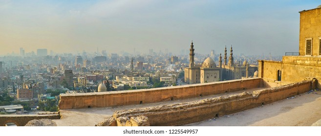 The view from the outer wall of Saladin Citadel on the Islamic Cairo with hazy residential quarters, Al Rifai' and Sultan Hassan Mosques on sunset, Egypt.