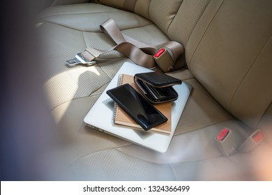 View from outside of the car at valuables wallet, purse laptop or computer notebook , credit card and mobile phone , Windows that are rolled down are open invitations for thieves to enter your vehicle