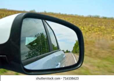 View from outside mirror of moving car over road