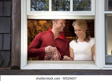 View from outside a window of a smiling couple doing dishes together in their kitchen. Horizontal format.