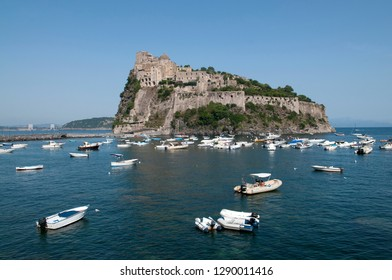 View over Aragonese Castle and boats in the sea at Ischia Ponte, on the island of Ischia, in the bay of Naples in Italy