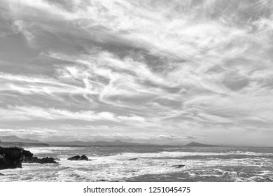 View over the Basque coast in Biarritz with bright soft clouds in the sky. Black and White photo.