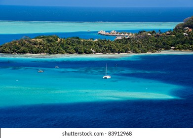 View over beautiful turquoise lagoon of bungalows, island and boats.  Tahiti, Society Islands, French Polynesia.