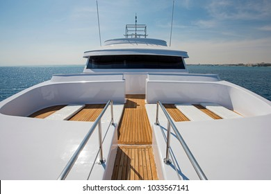 View over the bow of a large luxury motor yacht on tropical open ocean with bridge