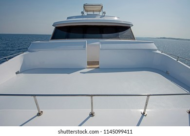 View over the bow of a large luxury motor yacht with flybridge on tropical open ocean
