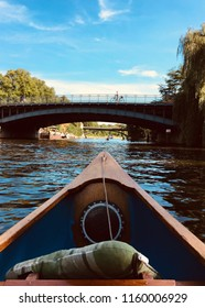 View over the bow of a wooden canoe looking out on a bridge crossing the river Alster in Hamburg on a beautiful summer day.