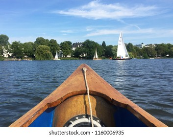 View over the bow of a wooden canoe on the river Alster in Hamburg on a beautiful summer day.