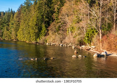 view over Burrard Inlet, ocean and island with boat and mountains in beautiful British Columbia. Canada.