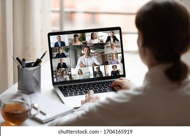 View over businesslady shoulder seated at workplace desk look at computer screen where collage of many diverse people involved at video conference negotiations activity, modern app tech usage concept
